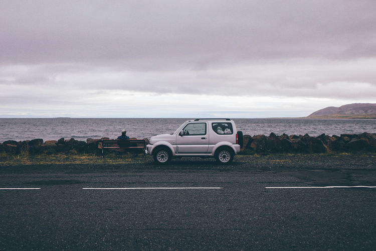 4x4 Cars Grey Day Iceland Man Sitting On Bench Beauty In Nature Car Cloud - Sky Clouds Day Grey Horizon Over Water Land Vehicle Landscape Nature No People Off-road Vehicle Outdoors Road Scenics Sea Seaview Sky Transportation