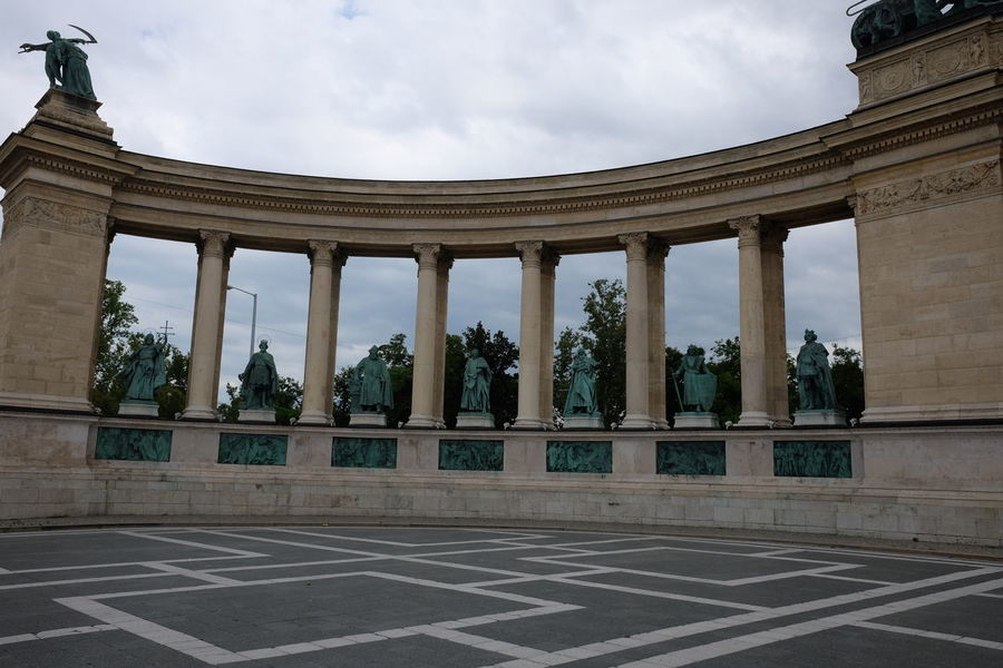 One of Two Semicircular Monuments at Millennium Monument, Hero's Square (designed by Gyorgy Zala representing War) Architectural Columns Architecture Bronze Statues Budapest Built Structure Capital City Cloudy Sky Composition Famous Place Full Frame Hero's Square History Hungary Millenium No People Outdoor Photography Semi Circular Building Stone Building Tourist Attraction  Travel Destination Trees War War Memorial