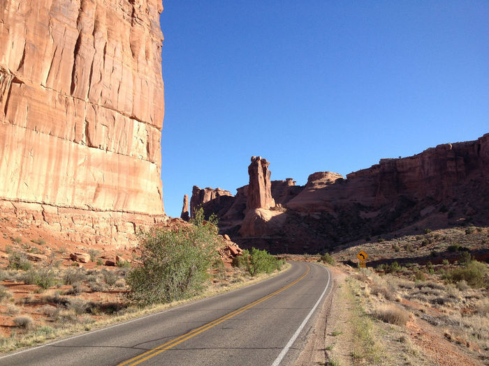 Road amidst rocky mountains at arches national park
