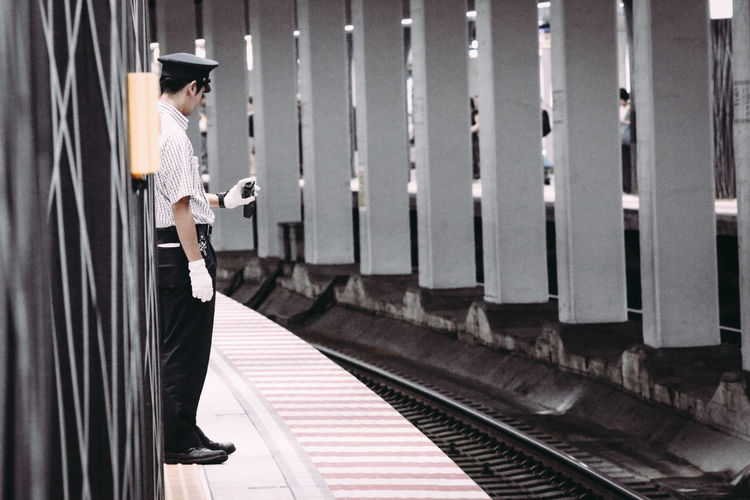 Side View Of Security Guard Standing On Railroad Station Platform