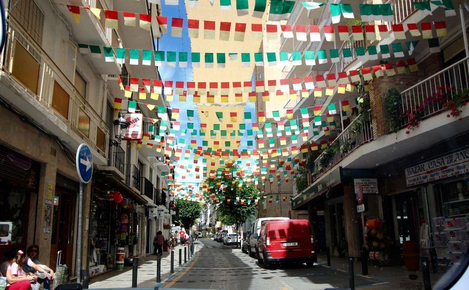 MeinAutomoment City Street Flags flags over the street in Lanjaron Alpujarra Granada Colorful City Original Experiences Original Artwork Beautiful View People Watching Sidewalks