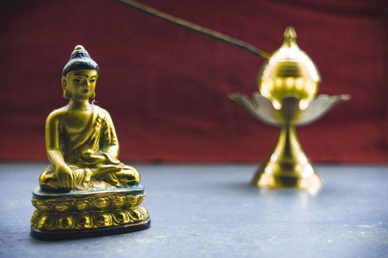 Close-up of buddha statue on table
