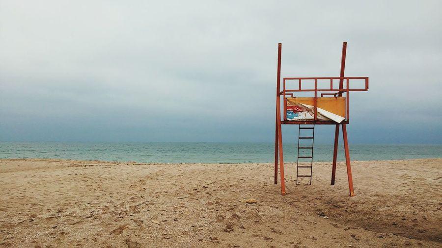 Empty lifeguard chair on beach against sky