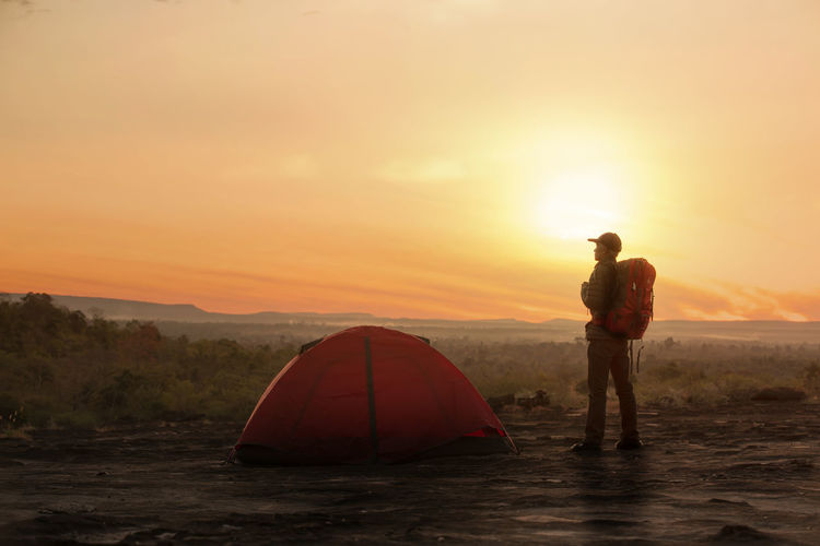 Backpacker with tent in camping site with sunset or sunrise backgroundv Sunset Sky Scenics - Nature Men Beauty In Nature Orange Color Adventure Real People Standing Leisure Activity Tranquility Nature Full Length Tranquil Scene Water Land People Two People Non-urban Scene Sun Outdoors Tent Camping