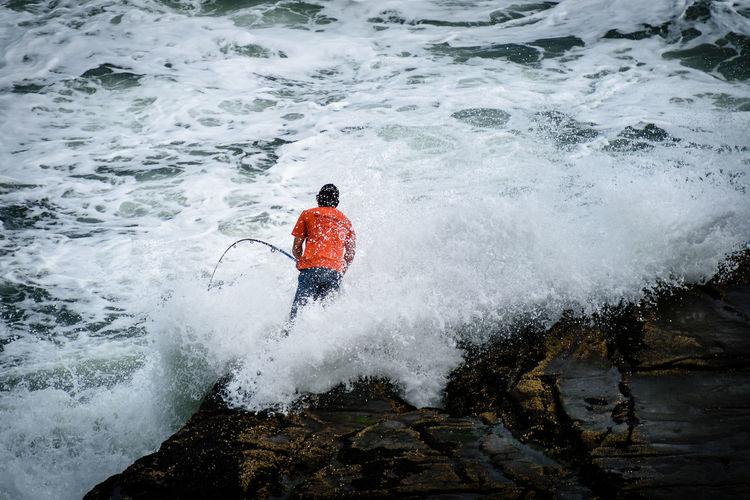 Rock fisherman braving crushing waves at auckland, new zealand muriwai beach
