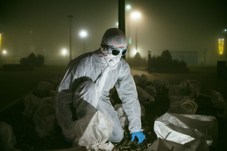 Full length of man wearing protective suit crouching outdoors at night