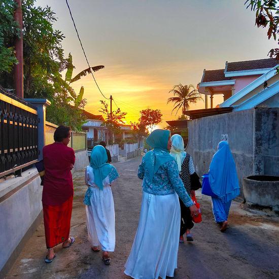 Rear view of people walking in temple against sky