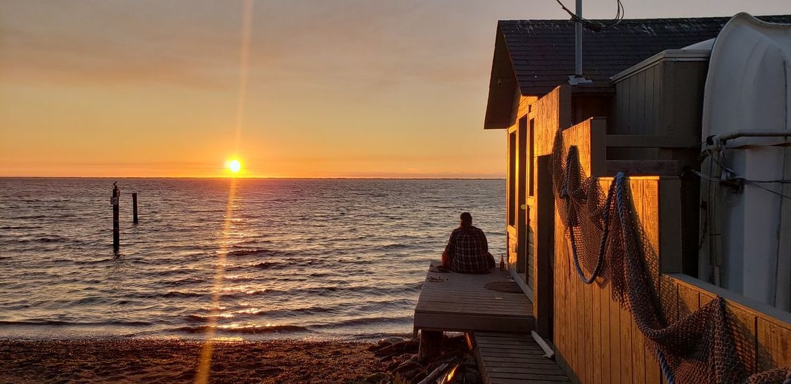 Sitting on the dock of the bay. Sunset Beach Reflection Lazy Days Summer Days person Girl EyeEm Selects Water Sea Sunset Beach Sun Wave Wood - Material Sky Lighthouse Seascape Tide Rocky Coastline Pier Lifeguard Hut Lifeguard  Marram Grass Coastal Feature Coastline Ocean Surf Low Tide Horizon Over Water Calm