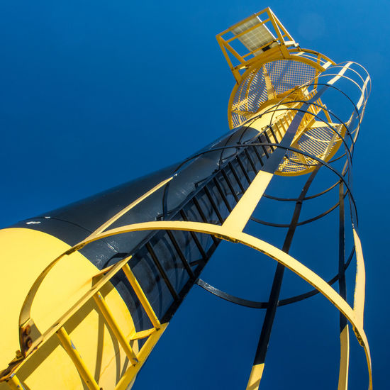 Lighttower perspective on a clear blue sky Anglet France Blue Clear Sky Close-up Day Diagonal Lighttower Low Angle View Nature No People Outdoors Part Of Seaside Sky Tall - High Urban Geometry Yellow Showcase June Fine Art Photography Premium Collection