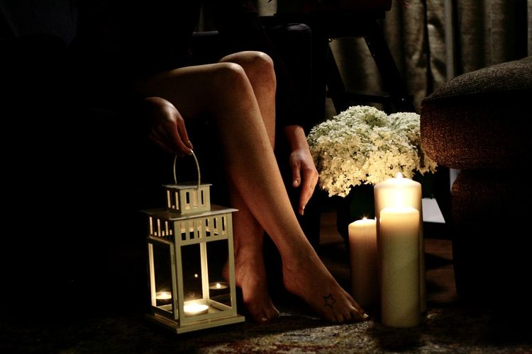 Midsection of person by illuminated candles on table