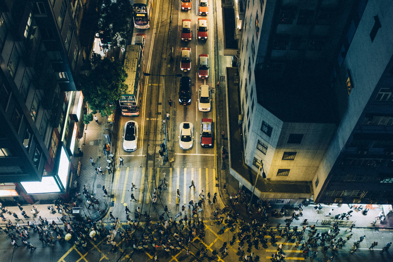 High angle view of crowd crossing city street by buildings at night
