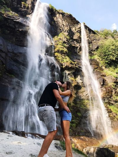 Side view of couple kissing while standing against waterfall