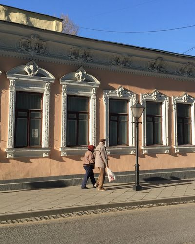People walking on street against building in city