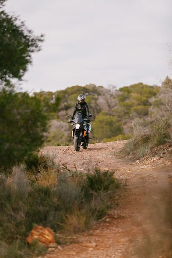 Rear view of man riding motorcycle on landscape against sky