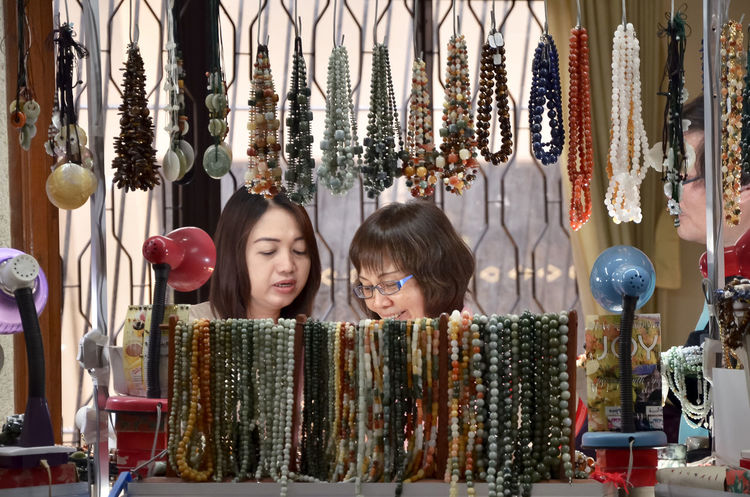 Abundance Business Buying Casual Clothing Choice Choosing Collection Consumerism Customer  Day For Sale Hanging Happiness Indoors  Jewelry Store Large Group Of Objects Real People Retail  Retail Display Small Business Smiling Store Togetherness Two People Variation