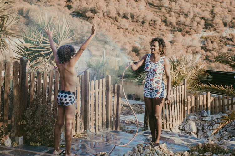 Mother spraying water on son while standing in yard