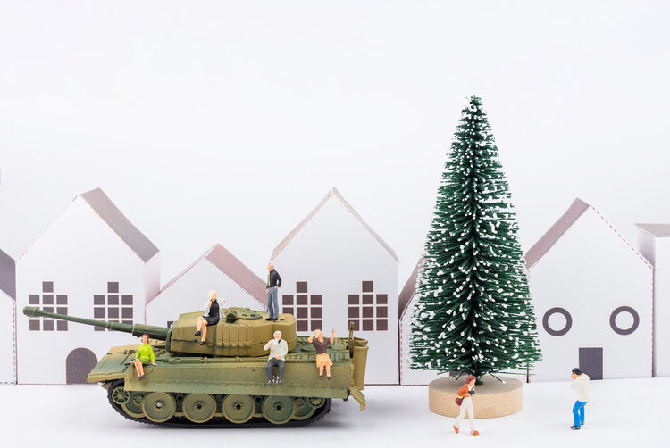 Close-Up Of Figurines With Christmas Tree And Toy Armored Vehicle Against White Background