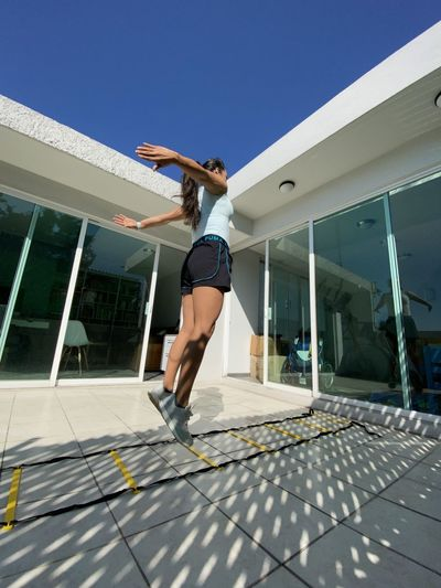 Mature woman exercising in front of house