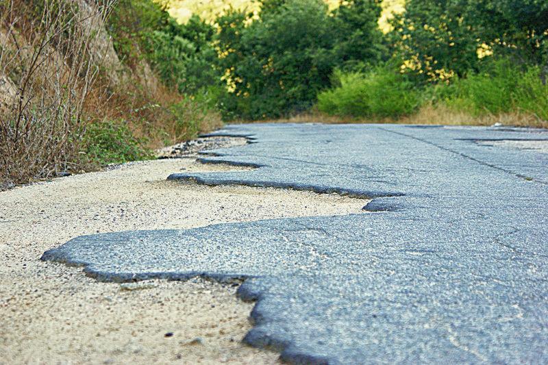 Route détruite par orages. Route Goudron Tree Oil Spill Water High Angle View Road Close-up