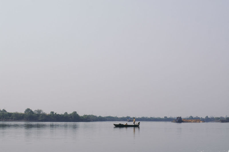 Boat sailing on river against clear sky