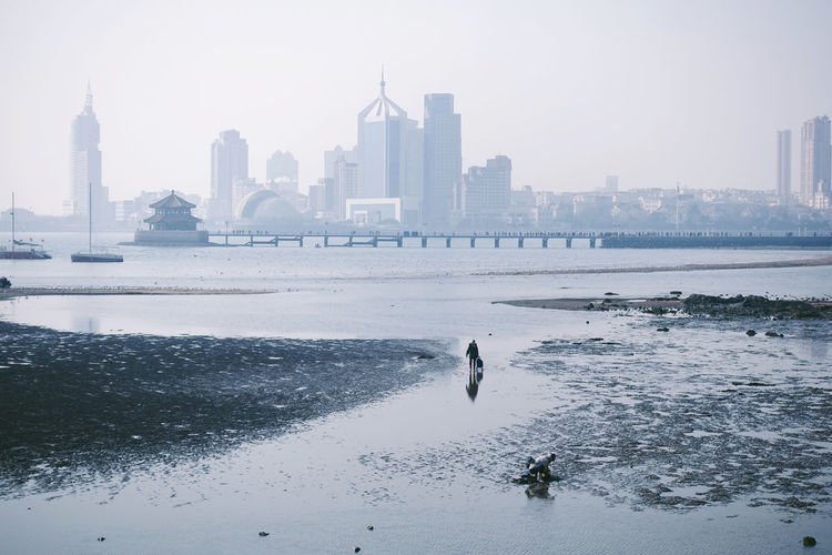 Landscape Horizon Over Water Horizon Sea City Cityscape City Life Lifestyles Life Water Skyscraper Building Urban Skyline Nature Outdoors Sky Architecture Building Exterior Sand Beach Coastline Real People Working China 17.62° My Best Photo