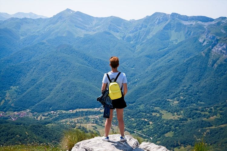 A woman looks at the valley from the top of a mountain