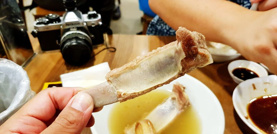 Holding boiled pork bone Hot Bowl Wood - Material Table Pork Bone Soup Camera Hand Holding Eating People Restaurant Water BIG Delicious Tasty EyeEm Selects EyeEmNewHere Human Hand Water Nail Polish Holding Close-up Served Finger Fine Dining Human Finger Dining Biting Prepared Food