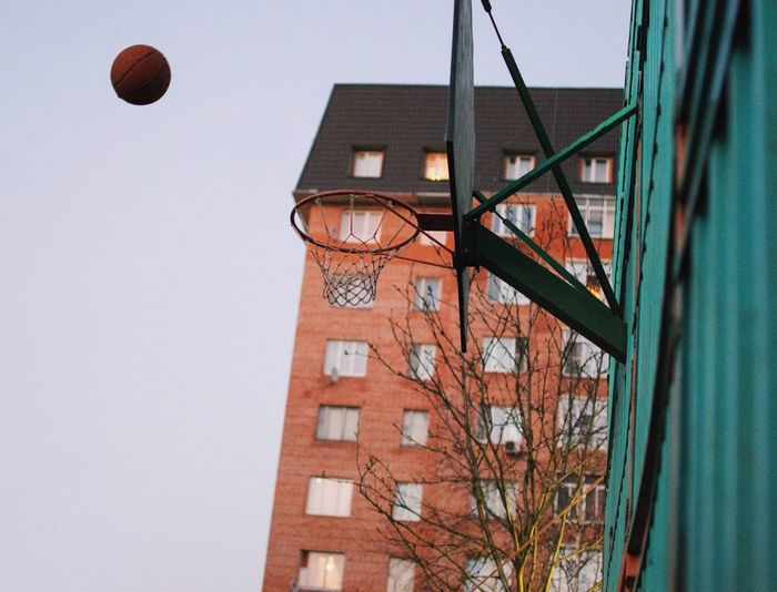 Low Angle View Of Basketball In Mid-Air Against Building