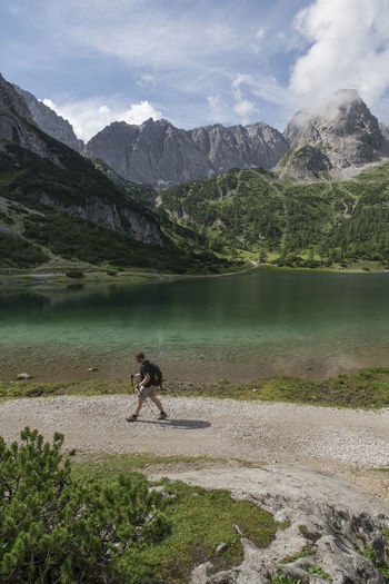 Side view of hiker walking against lake and mountains