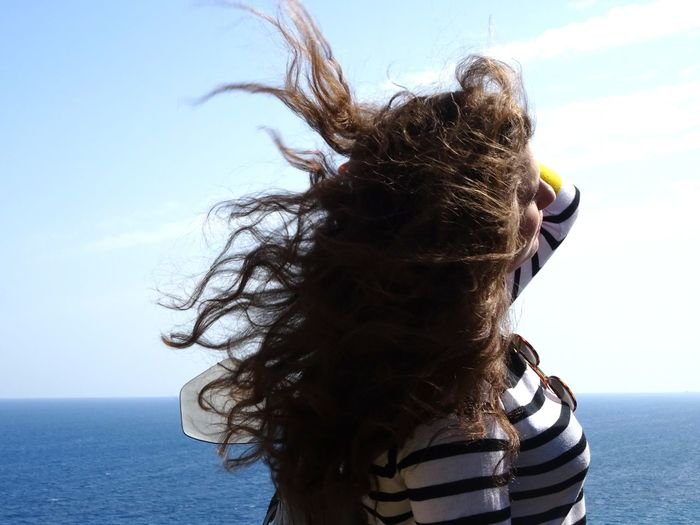 Side View Of Woman With Tousled Hair Standing By Sea Against Sky During Sunny Day
