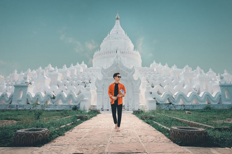 Portrait of man standing on temple against sky