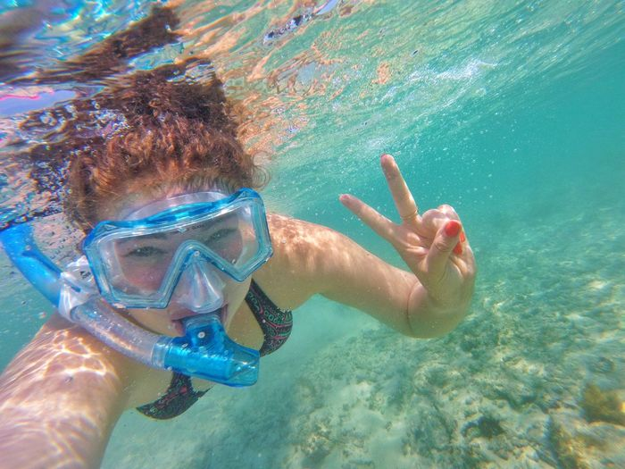 Portrait of woman gesturing peace sign while snorkeling in sea