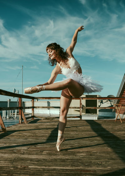 Full length of woman dancing on pier against sky