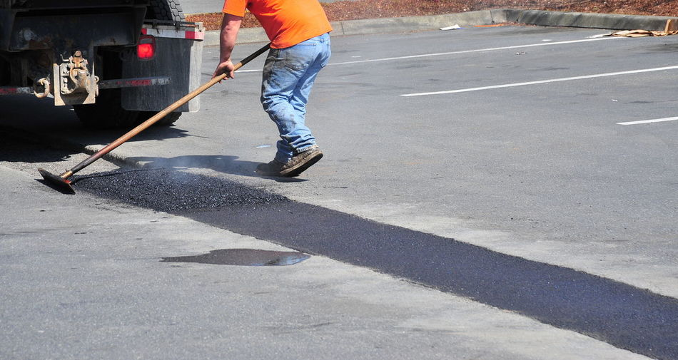 Man repairing potholes on the street.