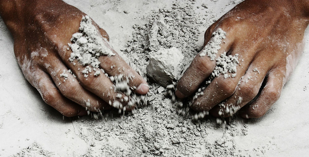 Cropped hands mixing cement