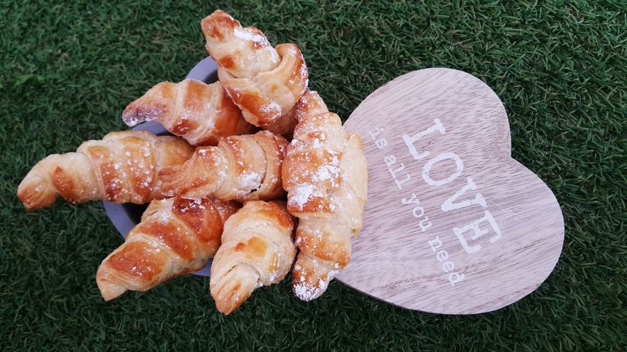 Close-up of croissants in container by text on heart shape over field
