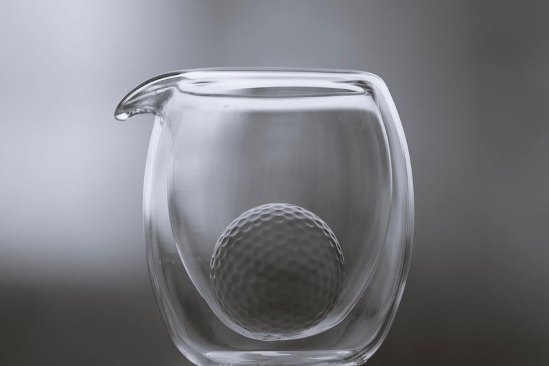 A monochrome picture of a golf ball in a glass jar Golf Golf Ball monochrome photography Monochrome Close-up Indoors  No People Single Object Glass - Material Studio Shot Transparent Silver Colored Focus On Foreground Gray Gray Background Glass Still Life Purity