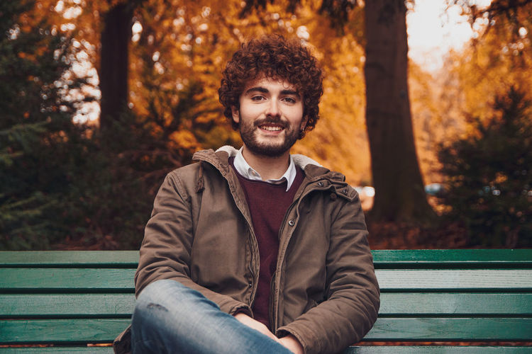 Portrait of young man sitting on bench