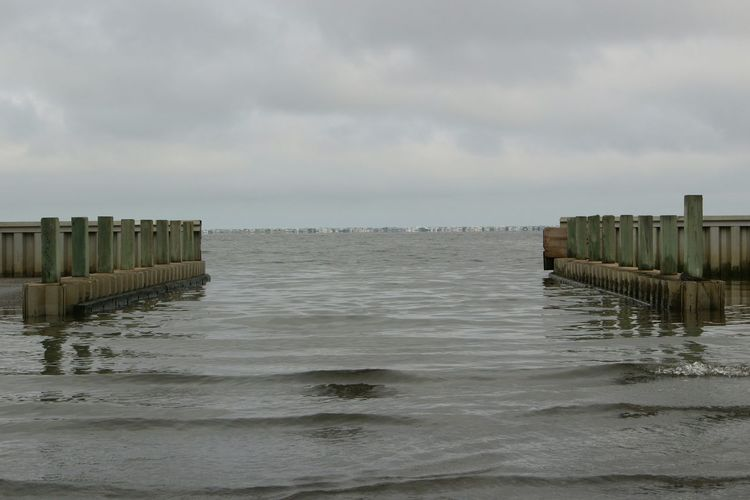 Wooden posts in sea against cloudy sky at dusk