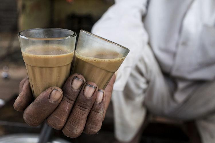 Hot chai (tea) from a street vendor in Ujjain, India. Beverage Brew Chai Dirt Dirty Fingers Dirty Hands Drink Drinking Glass Finger Nails Heat Hot Hot Beverage Human Hand Hygene India Indian Tea Male Man Hands Poor Hygene Tumbler Ujjain