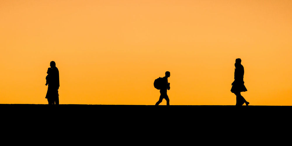 Silhouette People Walking Against Clear Sky During Sunset