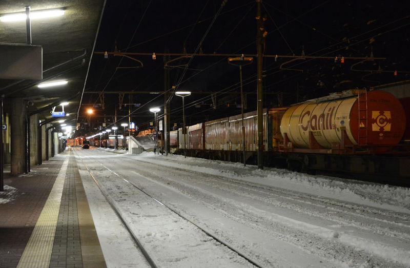 Train at railroad station during winter at night