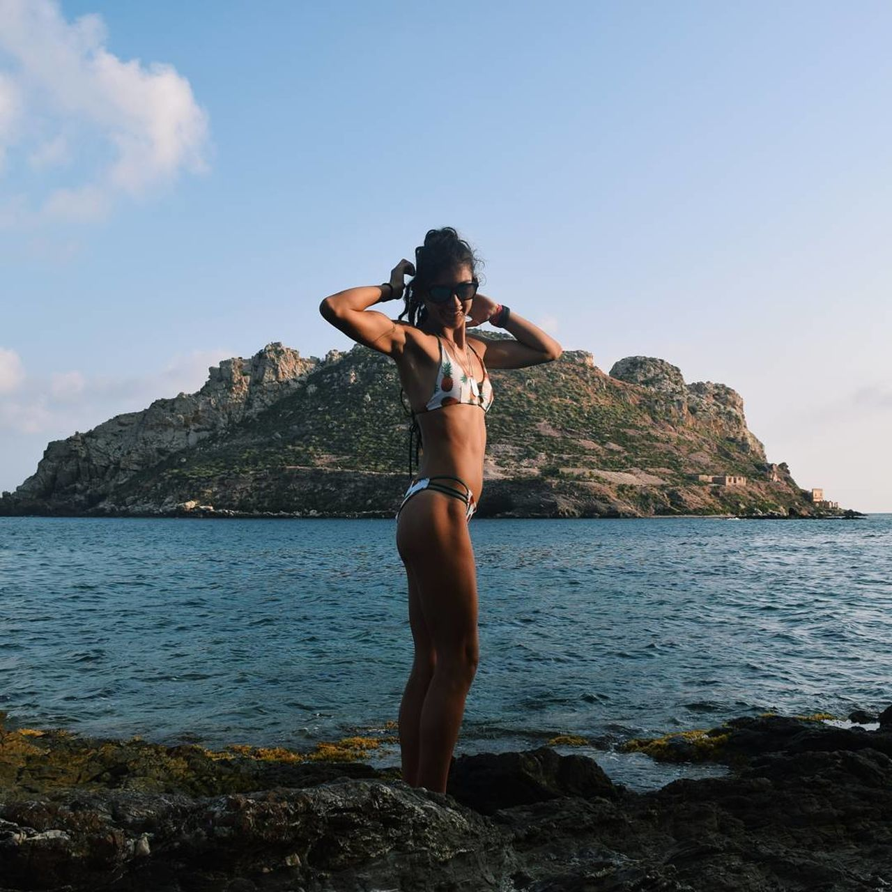 sea, rock - object, water, real people, one person, nature, lifestyles, full length, sky, beauty in nature, leisure activity, outdoors, young women, bikini, standing, day, scenics, young adult, mountain, beautiful woman