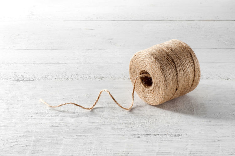 Reel of domestic coarse brown twine made from natural hemp fibers on a white wooden board with a single thread unwound in a spiral and copy space Household Natural String Twine Twisted Wood Brown Copyspace Cord Fiber Hemp Lying Down Reel Side View