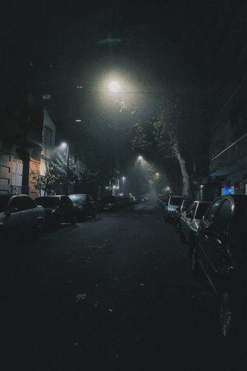 Illuminated city street at night during rainy season