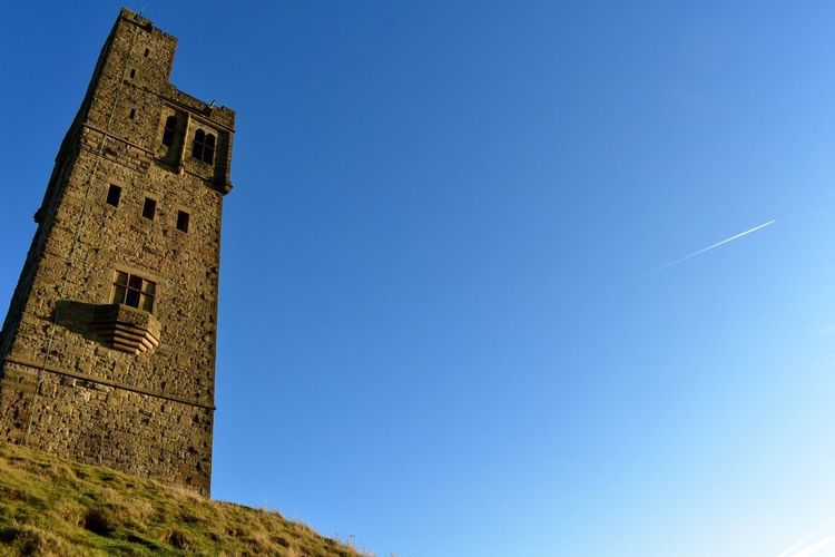 Low angle view of bell tower against clear blue sky