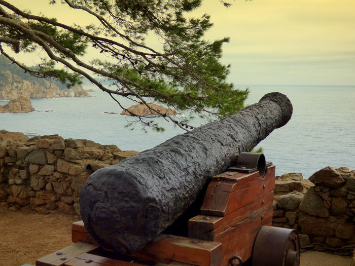 Cannon at fortress by sea against sky during sunset