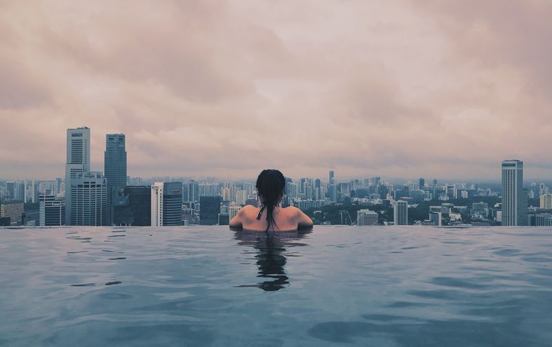 Rear view of woman in infinity pool against cityscape during sunset