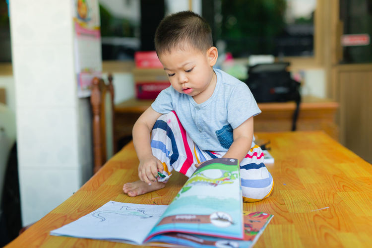 Boy With Book On Table At Home