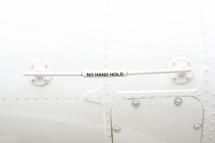 """The word """"No hand hold"""" wrote on the hand holder beware people is a part of the helicopter No People White Color Connection Metal Equipment Communication Text Hold Holder Helicopter Sign Signal Font Word No Hand Hold Warning Symbol"""